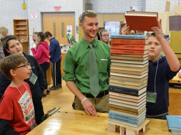 During a prior year's visit, technology education graduate student Nick Oetinger (center, with tie) works with Oswego Middle School seventh graders (from left) Damien Allen, Daniel Tomescu and Dalton Gibson on an experiment to see how many books they could stack on vertical folded index cards in a Wilber Hall lab.