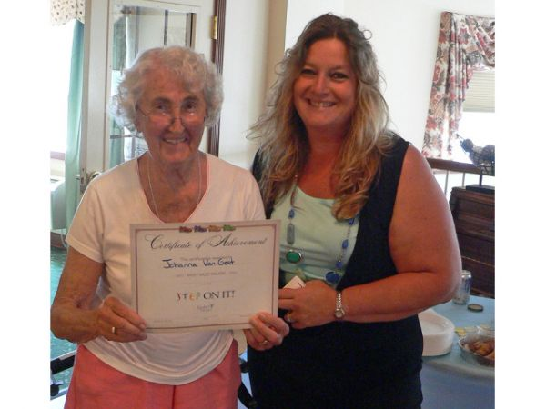 "Pictured (left to right) is Bishop's Commons resident Johanna Van Geet; with Kindred at Home Care Transitions Liaison Jennifer Rice, as she presents Johanna with her certificate of achievement as part of the ""Walk To Las Vegas Challenge"" celebration at Bishop's Commons."