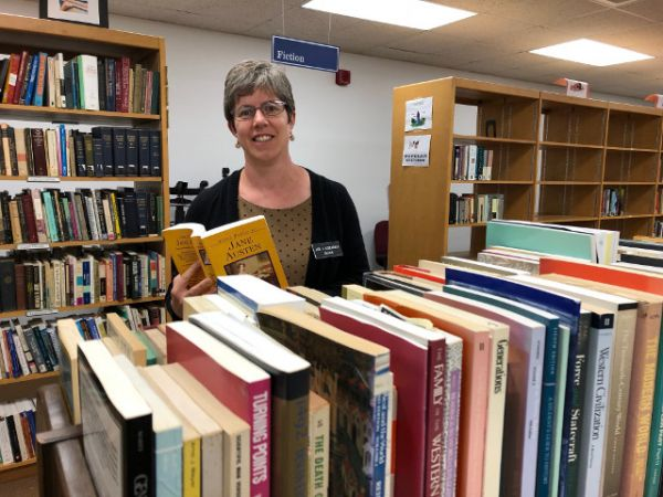 Finding books homes -- Sarah Weisman, director of SUNY Oswego's Penfield Library, looks over some of the selections that will be available for the library's book sale from 11 a.m. to 3 p.m. on Friday, Oct. 26, and Saturday, Oct. 27.